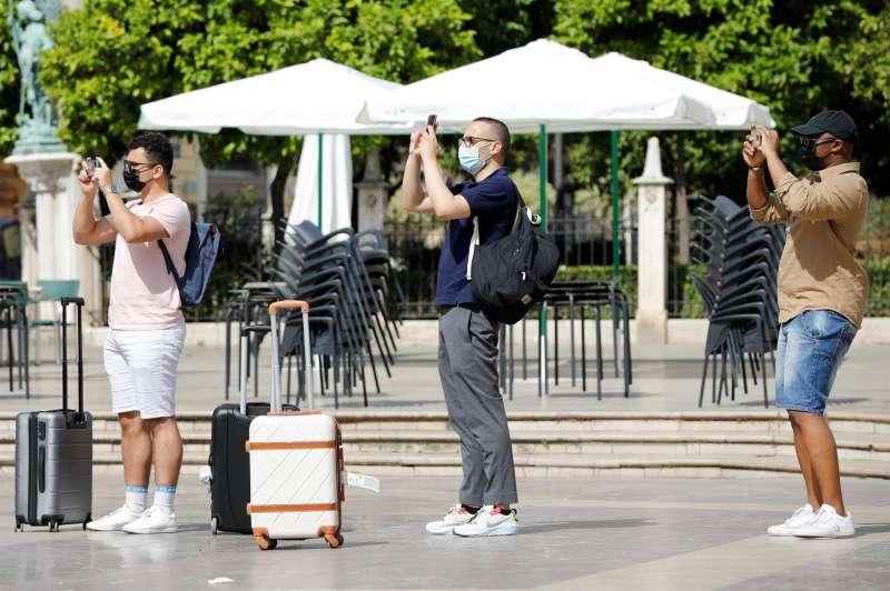 Tres turistas cargados con sus maletas realizan una foto en la plaza de la Virgen de València.