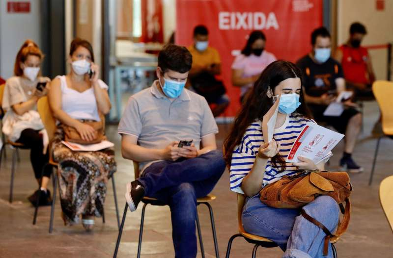 Varios j�venes esperan, en el Auditori de Castell�, su turno para recibir la primera dosis de la vacuna.