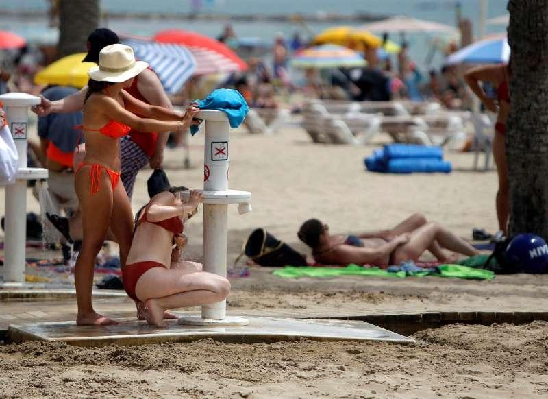 Dos mujeres tratan de refrescarse en los lavapaies de la playa de El Postiguet de Alicante.