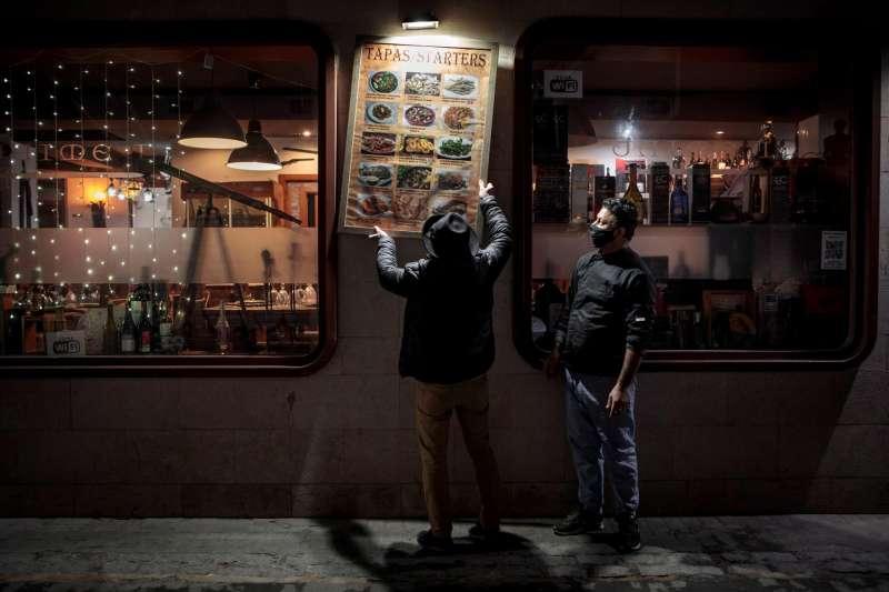 Unos trabajadores de un restaurante del centro de València recogen la terraza.