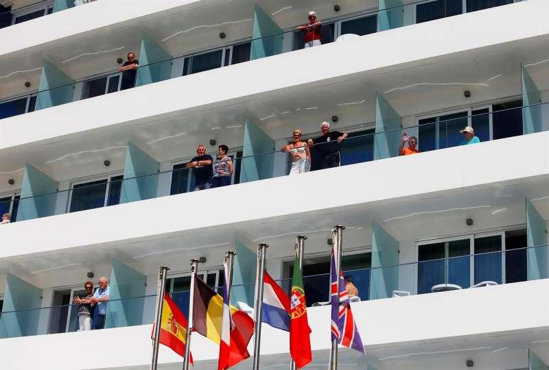 Varios turistas asomados a los balcones de su hotel en la playa de Benidorm (Alicante).