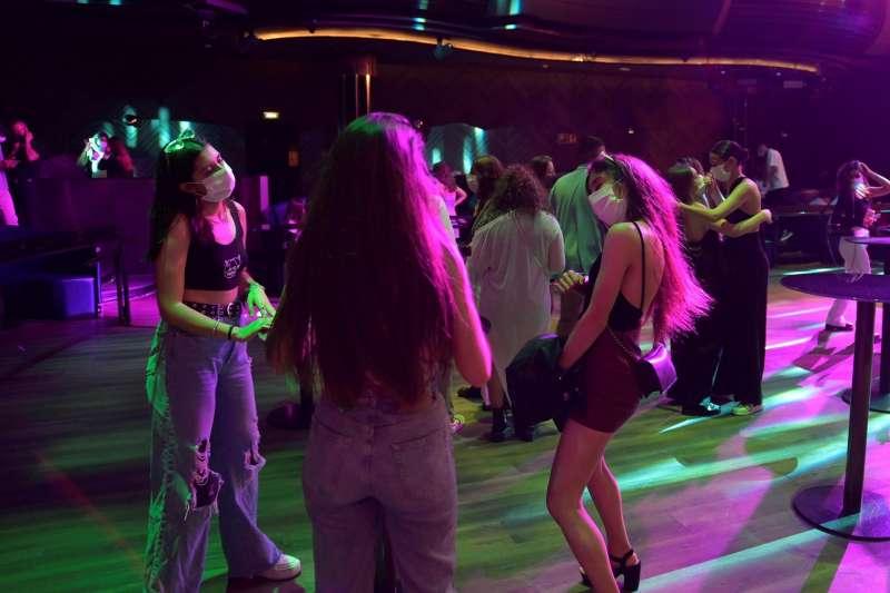 Varios jóvenes bailan en un local de ocio nocturno con mascarillas.