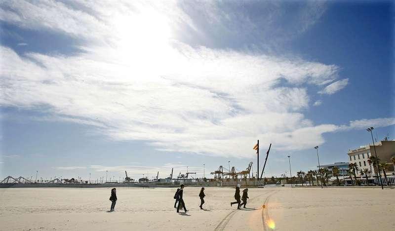 Varios jóvenes pasean por la playa de Las Arenas de Valencia.