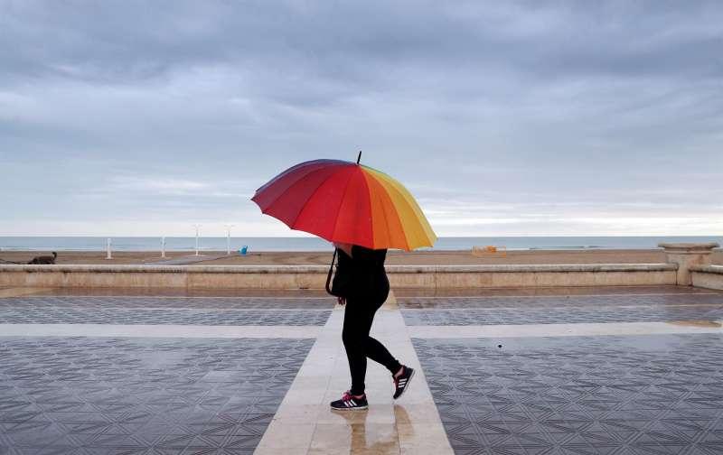 Una persona pasea por la playa protegida con un paraguas.