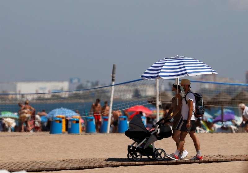 Dos personas caminan por una pasarela de la playa de La Malvarrosa de Valencia protegiéndose del intenso sol con una sombrilla.