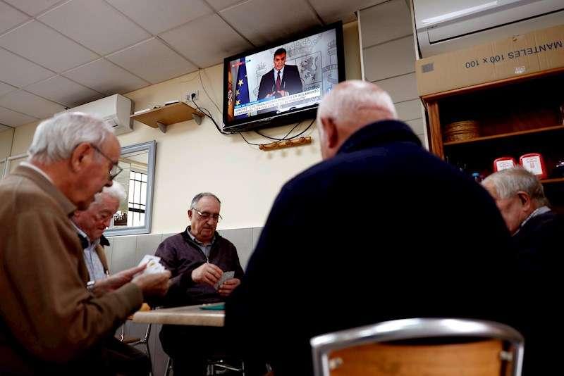 Un grupo de ancianos juega a las cartas, mientras en la televisión comparece el presidente del Gobierno. EFE