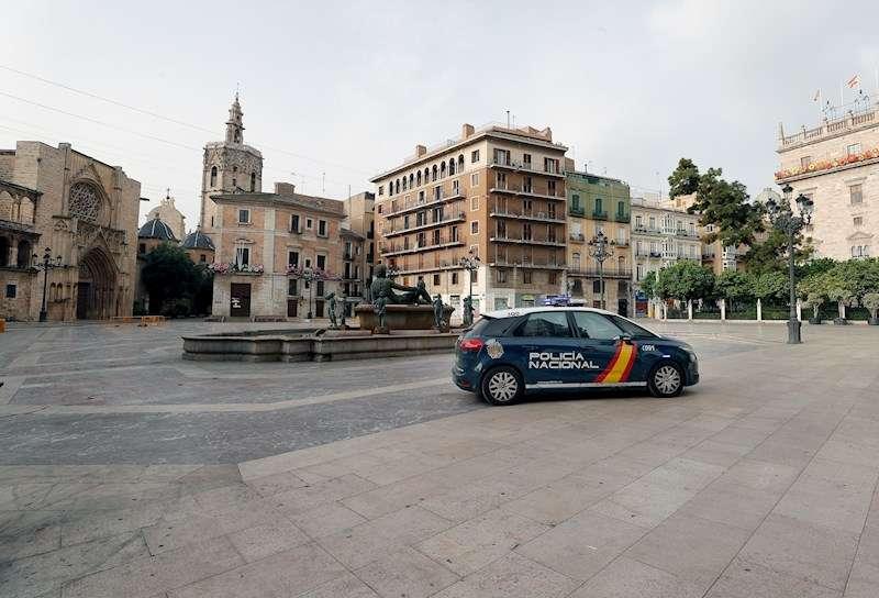 Un coche de la Policía Nacional vigila la plaza de la Virgen de València, en una imagen de estos días. EFE