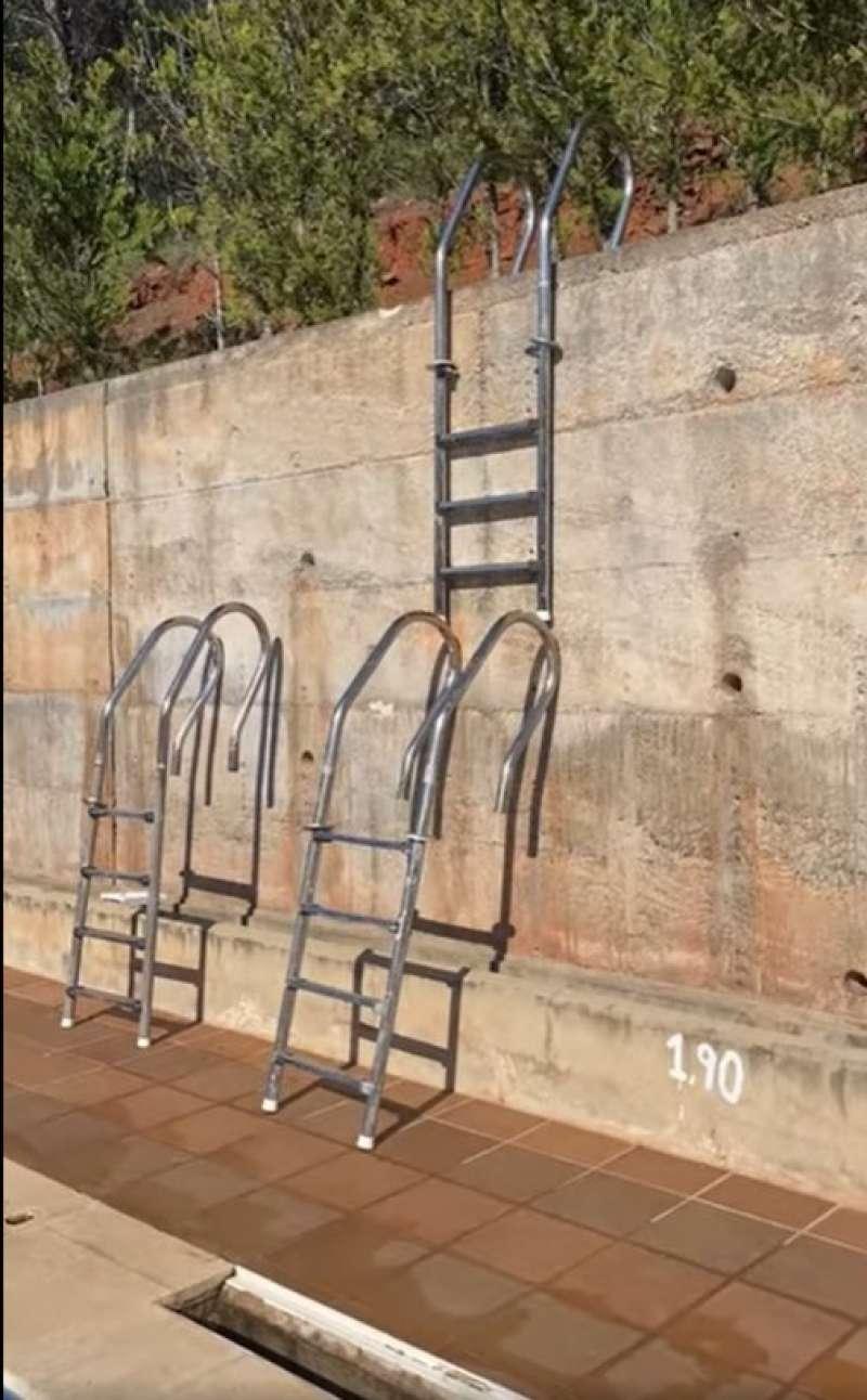 Imagen de las escaleras arrancadas de la piscina para trepar por el muro del polideportivo. / EPDA
