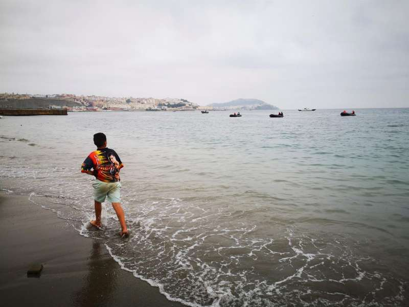 Un niño observa desde la playa de la localidad de Fnideq (Castillejos) uno de los espigones de Ceuta este martes