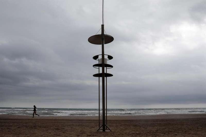 Una persona corre por una playa de València, en un día con nubes y amenaza de lluvia.
