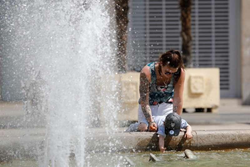 Una joven y un niño se refrescan en una fuente del centro de la ciudad. EFE/Ana Escobar/Archivo