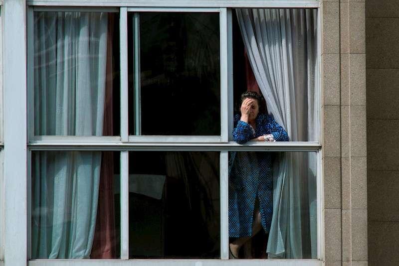 Una mujer asomada en la ventana de su vivienda durante el confinamiento por el Covid-19. EFE/Archivo