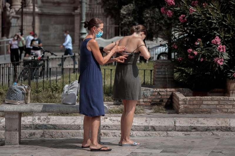 Dos jóvenes se aplican crema solar en una imagen de archivo tomada en una plaza del centro histórico de València.