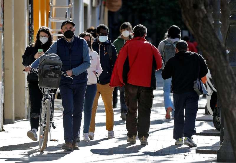 Varias personas protegidas con mascarillas por la ciudad de Valencia.