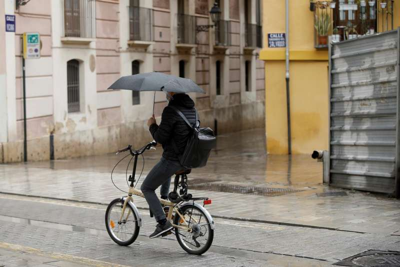 Una persona en bicicleta se protege de la lluvia en una imagen de archivo.