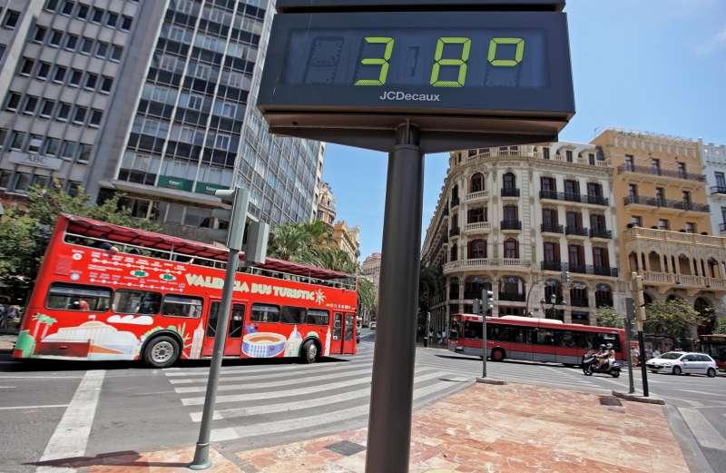 Un autobús turístico circula por el centro de la ciudad de ValÈncia ante un termómetro que marca 38º al sol. EFE/Manuel Bruque/Archivo