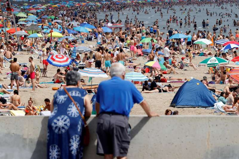 Una pareja contempla la playa de la Malvarrosa.