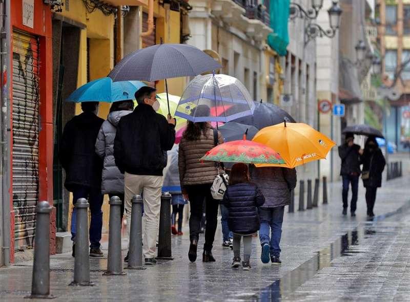 Un grupo de personas pasea un día lluvioso por València. EFE/Manuel Bruque/Archivo