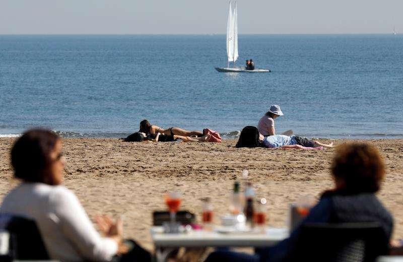 Imagen recurso de varias personas disfrutando en la playa.