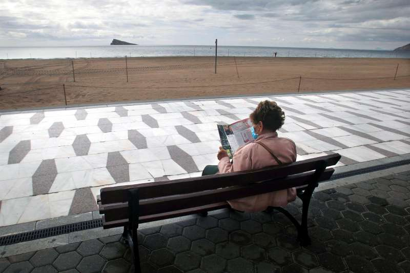 Una persona descansa en el paseo de la playa de Levante de Benidorm, prácticamente desierta.