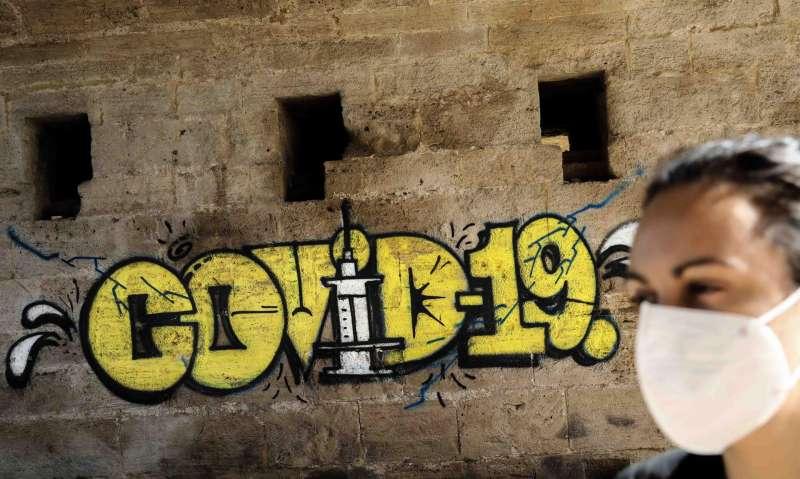 Una persona con mascarilla pasa ante un grafiti sobre el coronavirus. EFE/Ana Escobar/Archivo