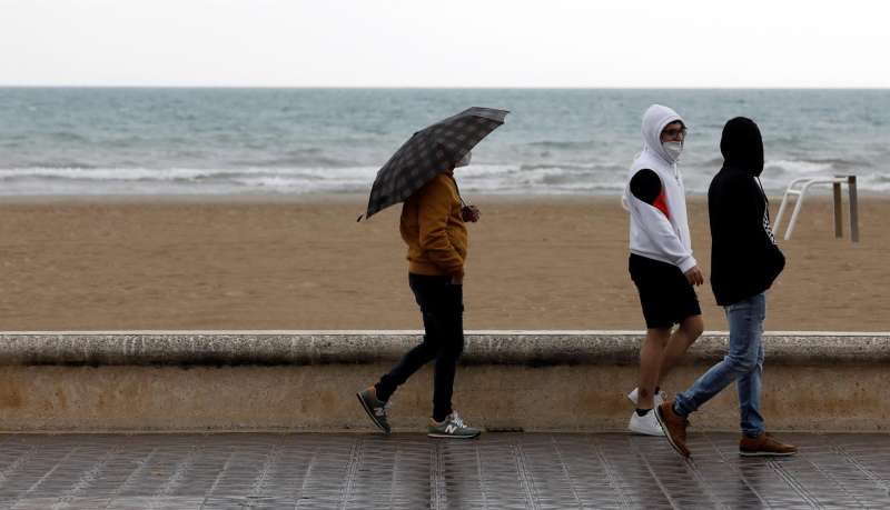 Un grupo de personas pasea por el paseo marítimo de la playa en un día lluvioso.