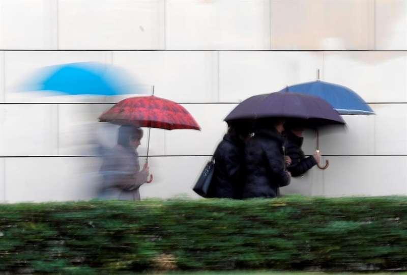Varias personas se protegen de la lluvia. EFE