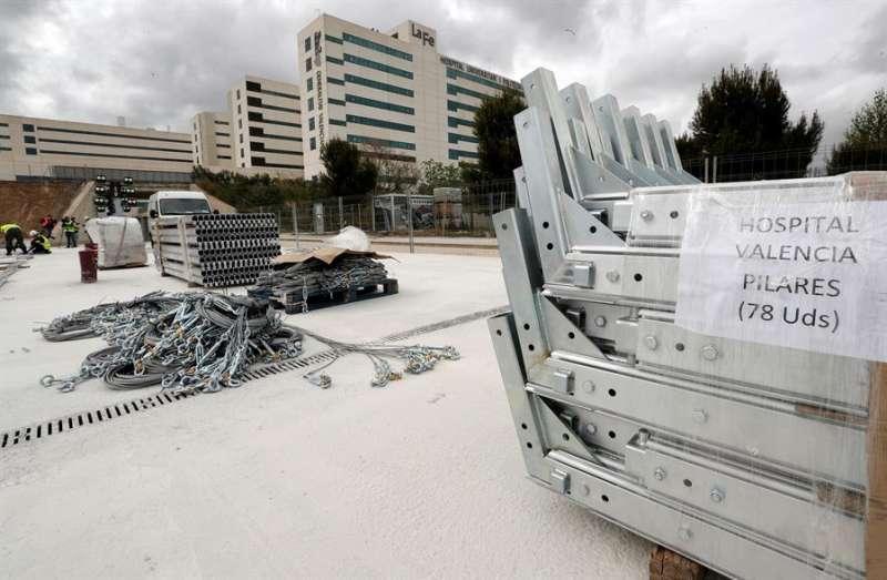 Un grupo de operarios trabaja en la obra del hospital de campaña de València, con 500 camas, que se está levantando junto al hospital La Fe, en una imagen de la tarde de este jueves. EFE/Juan Carlos Cárdenas