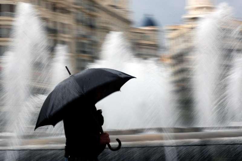 Una persona se resguarda con un paraguas en un día de lluvia.