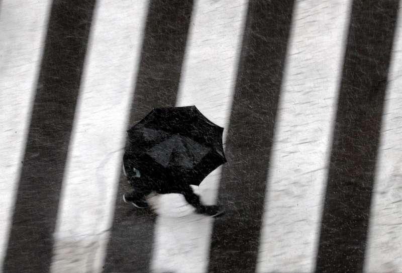 Una persona se protege con un paraguas de la lluvia.