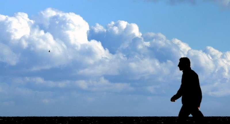 Un hombre pasea por la playa de la Malvarrosa