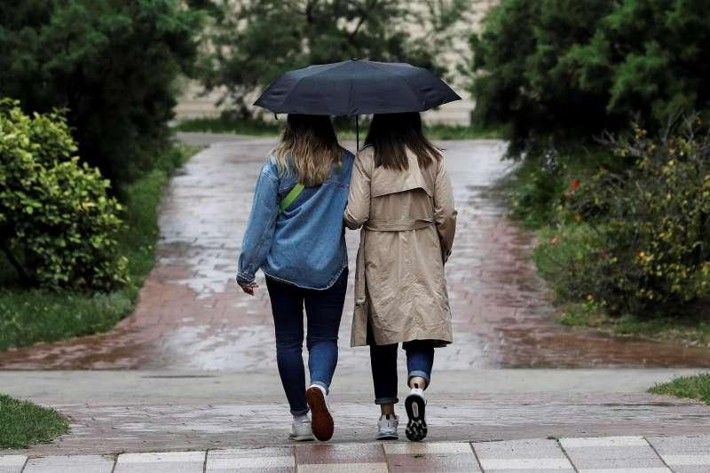 Dos personas se protegen de la lluvia con un paraguas, este martes en Valencia, cuando la Comunitat Valenciana registrará intervalos nubosos, con chubascos y tormentas por la tarde, localmente fuertes con granizo y más probable en el interior, y la visibilidad podría reducirse por polvo en suspensión y barro en las precipitaciones.