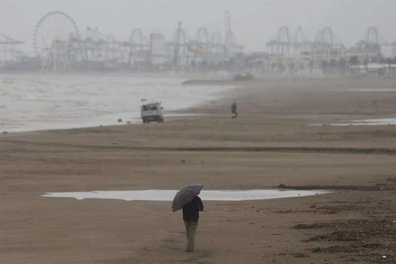 Una persona pasea por la playa en un día lluvioso. EFE/ Kai Forsterling/Archivo