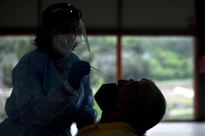 imagen de archivo de una trabajadora sanitaria realiza una prueba PCR a un hombre. EFE