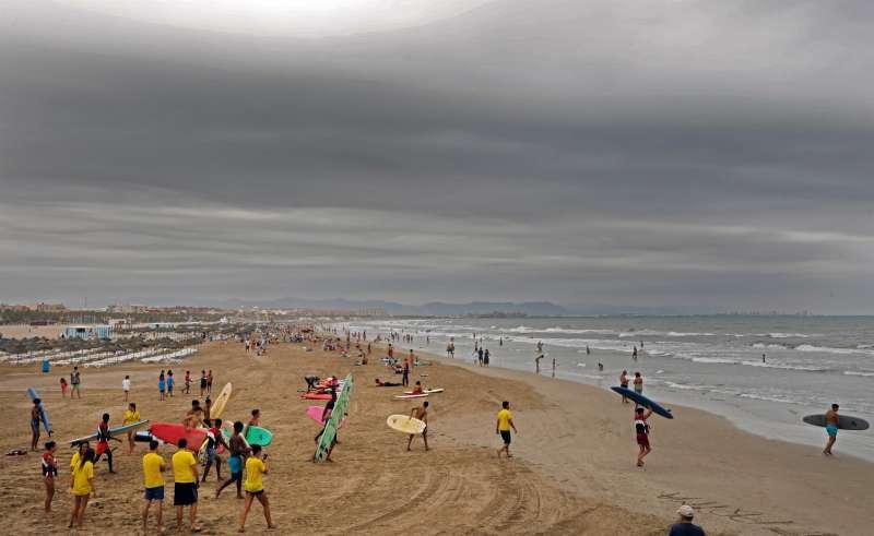 Un grupo de jóvenes entran en el mar con sus tablas de surf en la playa de la Malvarrosa de València en una imagen de archivo. EFE/ Juan Carlos Cárdenas /Archivo