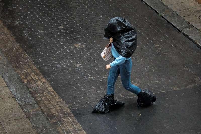 Una persona se protege de la lluvia.