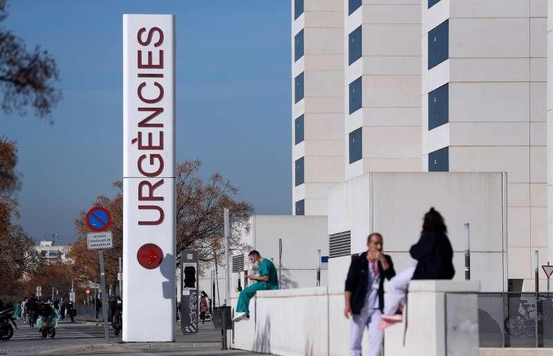 Personal sanitario del hospital La Fe de Valencia descansa a las puertas de urgencias del centro hospitalario. EFE/Manuel Bruque/Archivo