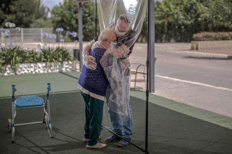 Imagen de archivo del 17/06/2020, en la que una interna en una residencia de mayores abraza a su hijo a través de un plástico.