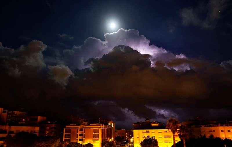 Los rayos y la luna llena iluminan el frente de nubes de la DANA en su llegada este lunes a la provincia de Alicante.