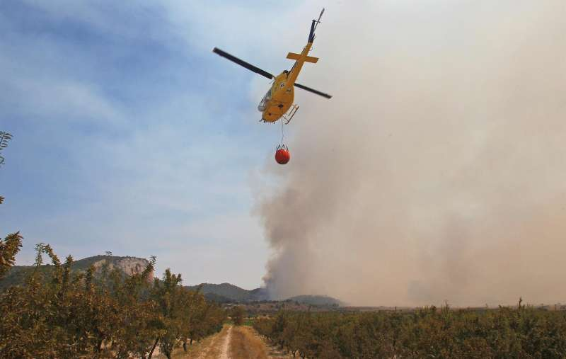 Un helicóptero se dirige al foco del Incendio forestal declarado entre las localidades alicantinas de Monóvar y La Romana en julio de 2020.