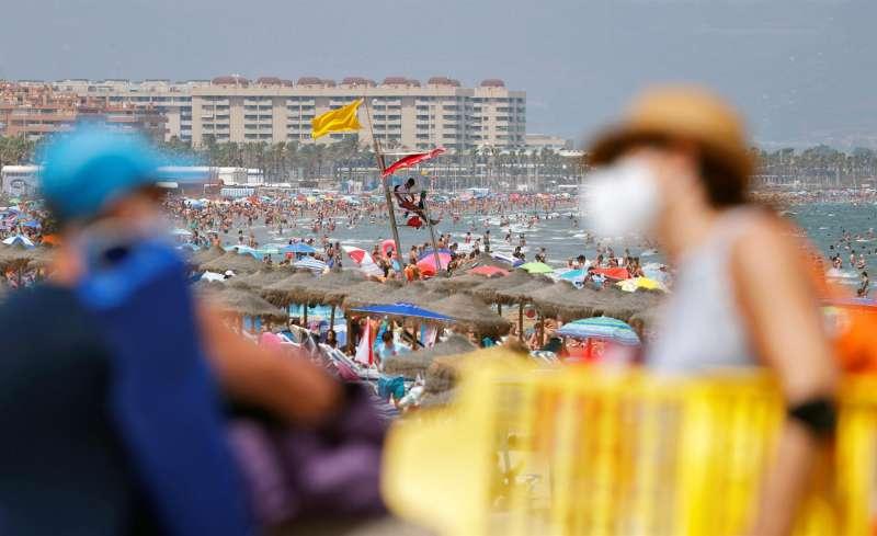 Dos personas conversan ante una abarrotada playa de Las Arenas de Valéncia.