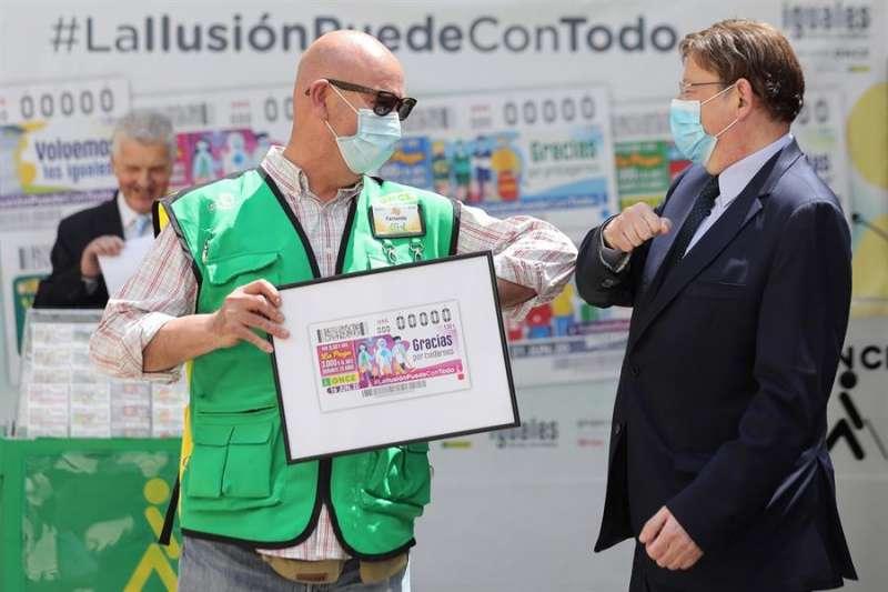 El president de la Generalitat, Ximo Puig, saluda al vendedor de la ONCE que le ha hecho entrega de una lámina conmemorativa de uno de los cupones de la ONCE. EFE
