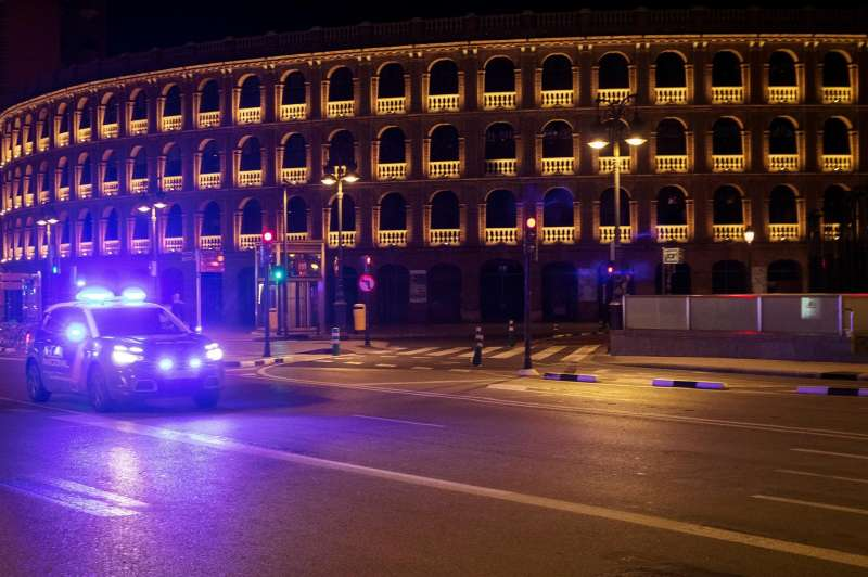 Un coche de policía circula junto a la plaza de toros durante el toque de queda. EFE/Kai Försterling/Archivo