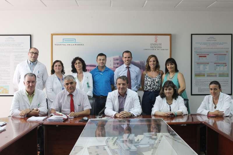 En la fotografía, el director gerente del Departamento de Salud de La Ribera, Dr. Javier Palau (centro con bata), y el director de Recursos Humanos de Ribera Salud, Salvador Sanchis (detrás con camisa azul), junto a los representantes sindicales.