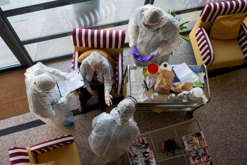 Atención a una anciana en una residencia, en estos días de pandemia. EFE