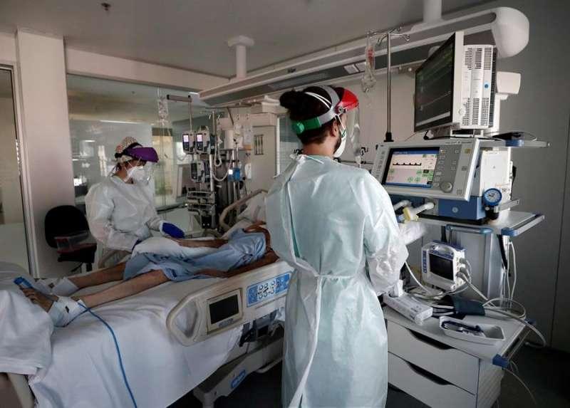 Dos profesionales sanitarios atienden a una persona en una UCI. EFE/Archivo