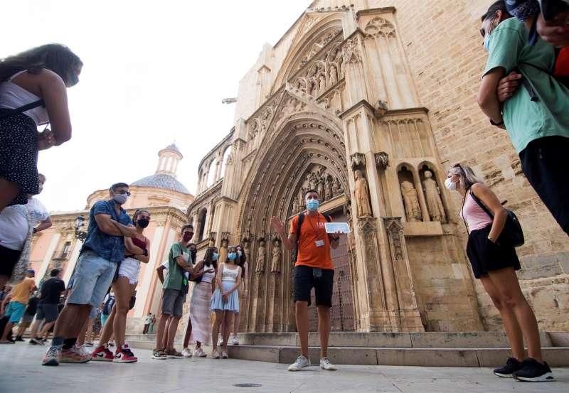 Un guía con mascarilla se dirige a un grupo de turistas frente a la puerta de los Apóstoles de la Catedral de València.