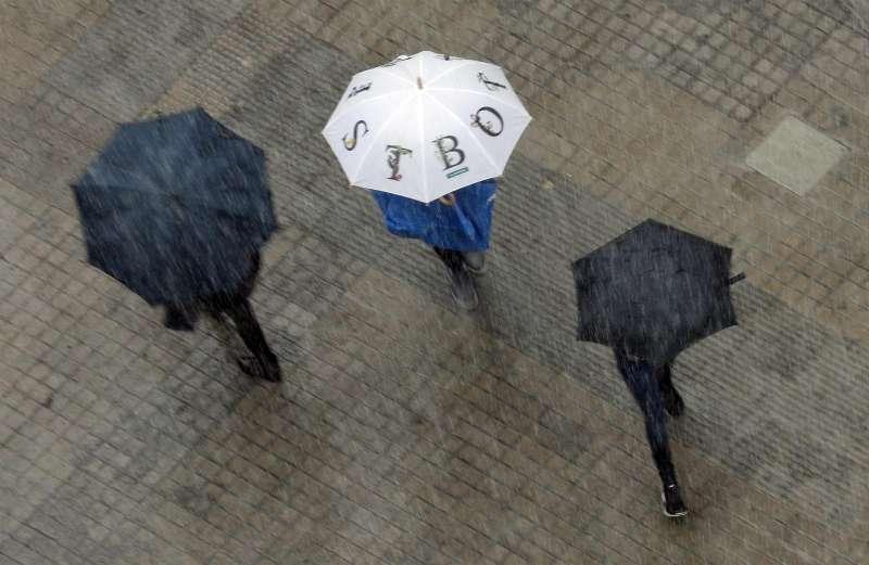 Varias personas se protegen con paraguas de la lluvia.