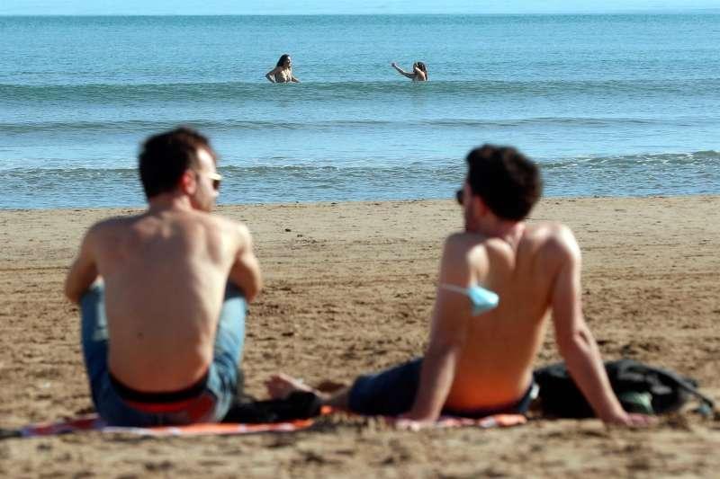 Dos personas se bañan en la playa de la Malvarrosa de Valencia en un día de calor. EFE