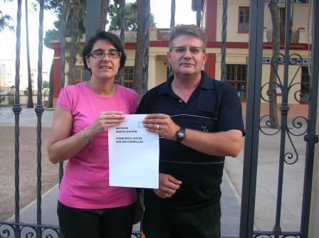 Los padres de Francisco Javier muestran uno de los informes en la puerta del colegio. Foto: EPDA.